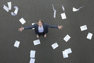 Papers falling on businessman standing on tarnac - PSTF00068
