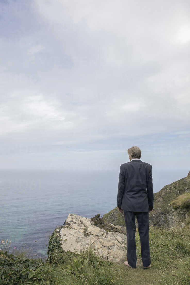 UK, Cornwall, Gwithian, businessman standing at the coast looking at view - PSTF00071 - Petra Stockhausen/Westend61