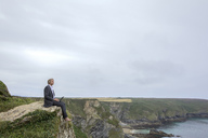 UK, Cornwall, Gwithian, businessman sitting at the coast using laptop - PSTF00077
