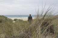 UK, Cornwall, Hayle, businessman standing in beach dunes looking at view - PSTF00080