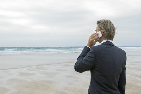 UK, Cornwall, Hayle, businessman on the beach talking on cell phone - PSTF00083
