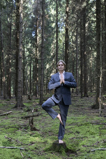 Businessman practicing yoga in forest - PSTF00089