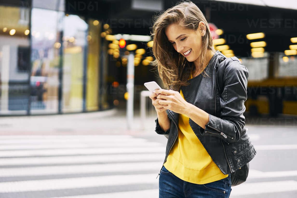 Happy woman looking at cell phone - BSZF00204 - Bartek Szewczyk/Westend61