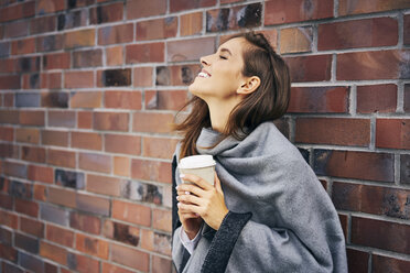 Happy woman with coffee to go in front of brick wall - BSZF00207