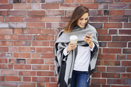 Happy woman with coffee to go looking at cell phone in front of brick wall - BSZF00210