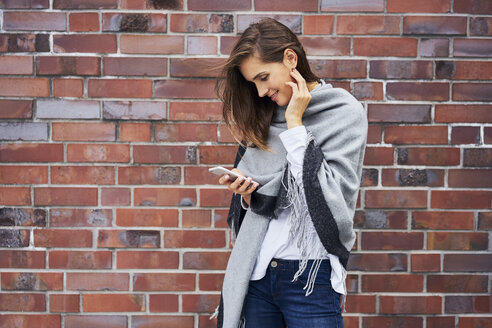 Smiling young woman looking at cell phone in front of brick wall - BSZF00213