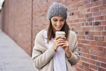 Happy woman with coffee to go - BSZF00216