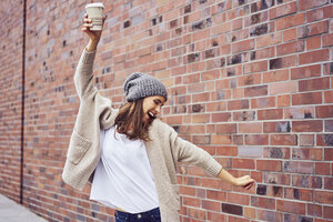 Happy woman with coffee to go singing and dancing on the street - BSZF00219