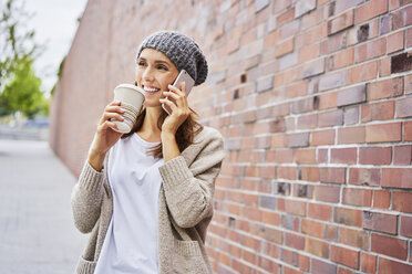 Portrait of happy woman with coffee to go on the phone - BSZF00222