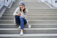 Happy woman with coffee to go sitting on stairs looking at cell phone - BSZF00225