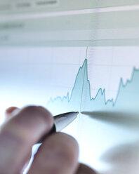 Hand of a stock broker analysing line graph on computer screen - ABRF00068