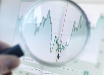 Investor analysing line graph on computer screen with magnifying glass - ABRF00071