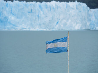 Argentina, Patagonia, El Calafate, Argentinian Flag with Glacier Perito Moreno in the background - AMF05619