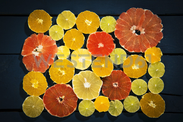 Sliced citrus fruits on black ground - MAEF12513