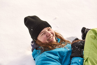 Laughing young woman lying in the snow - JEDF00299