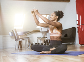 Smiling young woman sitting on yoga mat taking a selfie - MADF01371