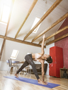 Young woman practicing yoga in attic - MADF01377