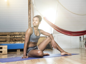 Young woman sitting on yoga mat having a break - MADF01383