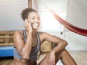 Happy young woman in sportswear on cell phone - MADF01386