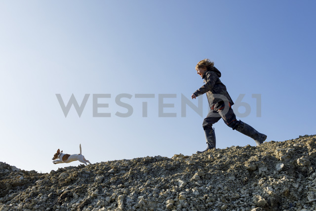 Happy boy running with dog under blue sky - KMKF00152