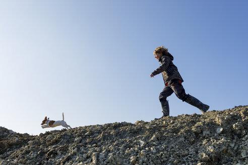 Happy boy running with dog under blue sky - KMKF00152