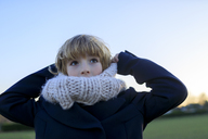 Boy with knitted round scarf at sunset - KMKF00155