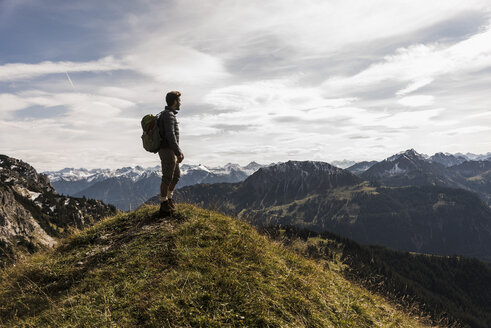 Austria, Tyrol, young man standing in mountainscape looking at view - UUF12555