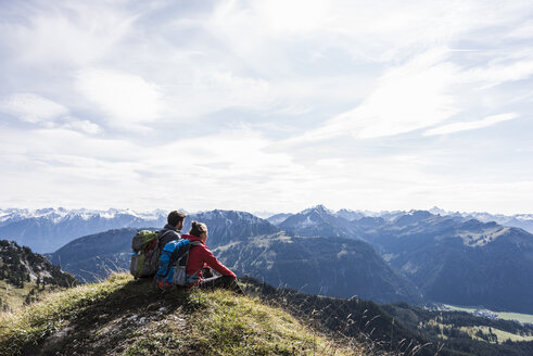 Austria, Tyrol, young couple sitting in mountainscape looking at view - UUF12564