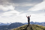 Austria, Tyrol, young woman standing in mountainscape cheering - UUF12570