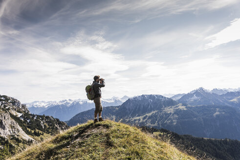 Austria, Tyrol, young man standing in mountainscape looking at view with binoculars - UUF12573