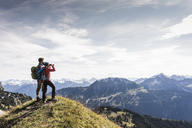 Austria, Tyrol, young couple standing in mountainscape looking at view - UUF12576