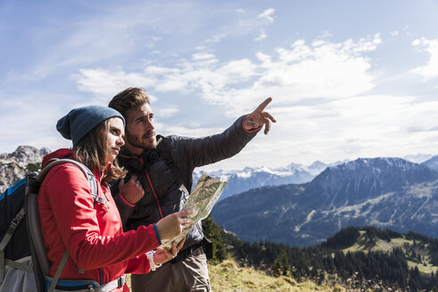 Austria, Tyrol, young couple with map in mountainscape looking around - UUF12582