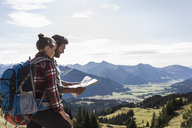 Austria, Tyrol, young couple looking at map in mountainscape - UUF12591