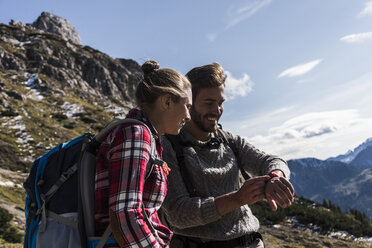 Austria, Tyrol, smiling young couple looking at watch in mountainscape - UUF12594