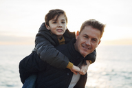 Portrait of father carrying son piggyback on the beach - EBSF02023