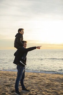 Father carrying son piggyback on the beach at sunset pointing finger - EBSF02032