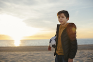 Portrait of boy holding football on the beach at sunset - EBSF02035