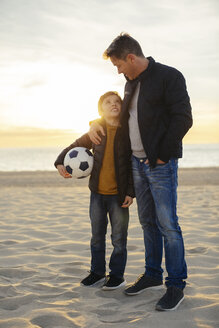 Father embracing son with football on the beach at sunset - EBSF02038
