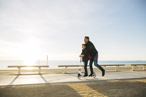 Father and son riding scooter on beach promenade at sunset - EBSF02047