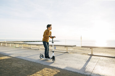 Boy riding scooter on beach promenade at sunset - EBSF02059