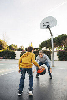 Father and son playing basketball on an outdoor court - EBSF02062