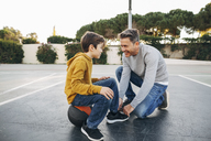 Father lacing son's shoe on basketball outdoor court - EBSF02065
