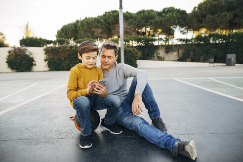 Father and son sitting on basketball outdoor court using cell phone - EBSF02068