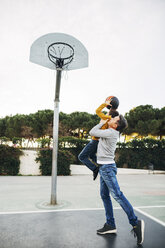Father lifting up son on basketball outdoor court - EBSF02071