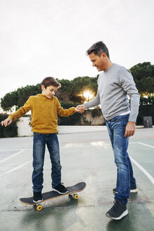 Father assisting son riding skateboard - EBSF02074