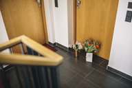 Farewell flowers, candle and condolende card at apartment door of deceased neighbour - MFF04381