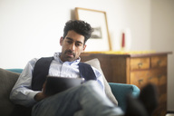Portrait of relaxed man sitting on couch at home using tablet - SGF02149