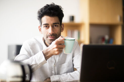 Portrait of relaxed businessman with mug at desk in the office - SGF02155