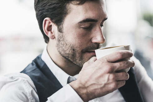 Relaxed young man drinking cup of coffee - UUF12619