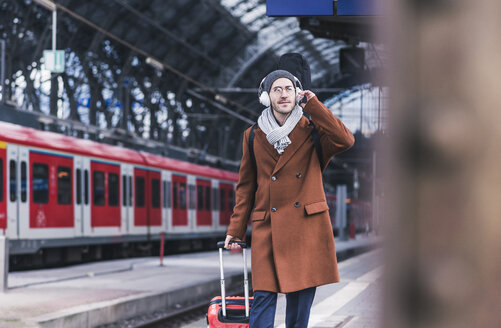 Young man with guitar case and headphones at station platform - UUF12622